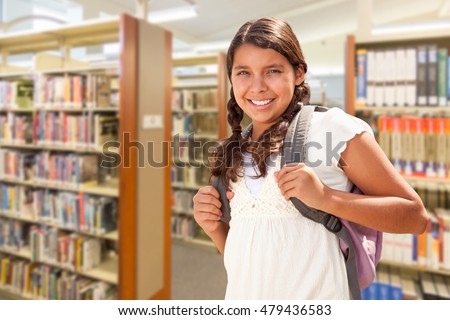 Happy Hispanic Girl Student Wearing Backpack Walking in the Library.