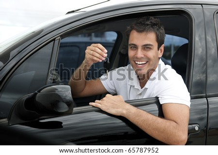 Happy hispanic man showing the key of his new car