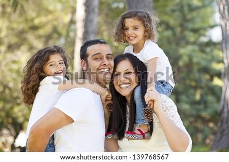 happy hispanic people parents giving children piggyback