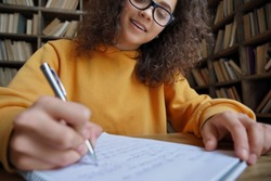 Happy hispanic teen girl school or college student writing in workbook doing homework or preparing for exam in library sitting at desk. Learning math and individual schoolwork concept, close up view.