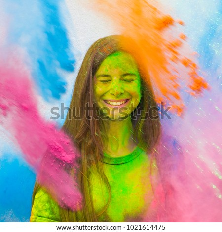 Happy holi. Young cheerful girl under explosion of colored powder at Holi colors (paints) party. Freeze motion (stop motion) of color powder exploding or throwing colour powder. Glitter explosion. #1021614475