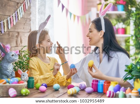 Happy holiday! A mother and her daughter are painting eggs. Family preparing for Easter. Cute little child girl is wearing bunny ears. #1032955489