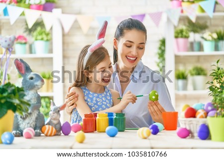 Stock Photo Happy holiday! A mother and her daughter are painting eggs. Family preparing for Easter. Cute little child girl is wearing bunny ears.