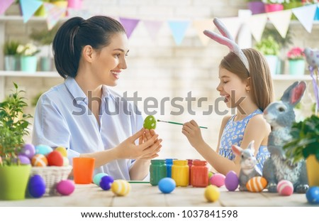 Happy holiday! A mother and her daughter are painting eggs. Family preparing for Easter. Cute little child girl is wearing bunny ears. #1037841598