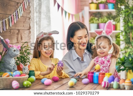 Happy holiday! A mother and her daughters are painting eggs. Family preparing for Easter. Cute little children girls are wearing bunny ears. #1029370279