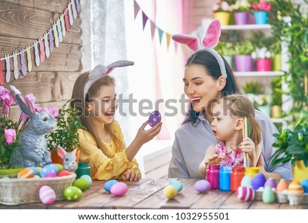 Happy holiday! A mother and her daughters are painting eggs. Family preparing for Easter. Cute little children girls are wearing bunny ears. #1032955501