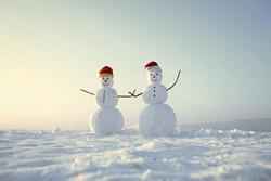 Happy holiday and celebration. New year snowmen from snow in santa hat. Snowman couple outdoor. Santa claus hat in winter. Christmas or xmas decoration.