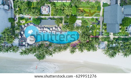 Happy Holiday in Asia, Swimming Pool surrounding palms and green garden in the beautiful tropical resort, aerial top view