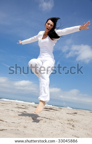 Happy holiday jumping woman on the beach with outstretched arms and smiling positive expression