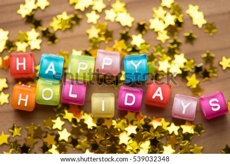 Happy Holidays. Colorful alphabet cubes with gold stars. Shallow depth of field. #539032348