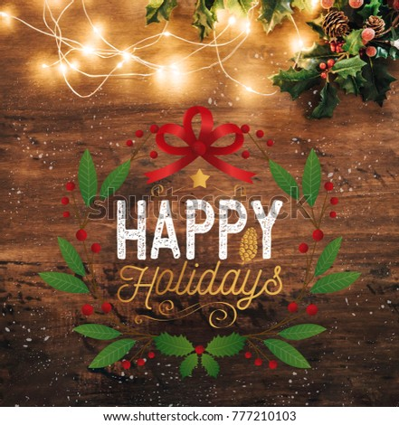 Happy holidays image with wooden background and lights and decoration on top #777210103