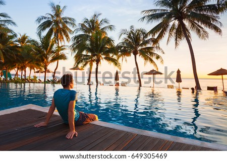 happy holidays in beautiful beach hotel at sunset, man sitting near swimming pool and relaxing #649305469