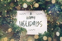 Happy holidays text, card concept. Holiday background with white card in the middle of evergreen tree branches with lights, christmas and festive season idea, minimalistic design