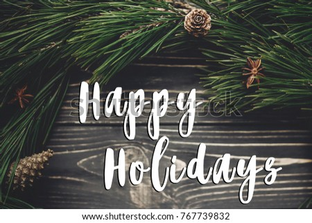 happy holidays text sign, greeting card. stylish christmas rustic wreath flat lay. green tree fir branches and pine cones anise top view on rustic wooden background. seasonal greetings