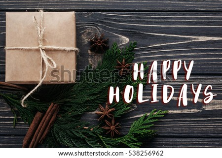 happy holidays text sign on christmas present box and fir branches with cinnamon and anise on rustic wooden background. flat lay. seasonal greetings concept. winter holidays #538256962