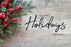 Happy Holidays Text with Christmas Evergreen Branches and Berries in Corner Over Rustic Wooden Background