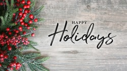 Happy Holidays Text with Holiday Evergreen Branches and Berries in Corner Over Rustic Wooden Background
