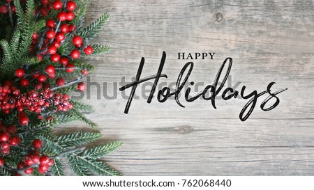 Happy Holidays Text with Holiday Evergreen Branches and Berries in Corner Over Rustic Wooden Background #762068440
