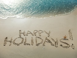 Happy Holidays! Written in sand at the beach. Holiday concept.
