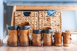 Happy home family concept. Small and big yellow boots together. Leather tourist boots. Shoes of father, mother and a child