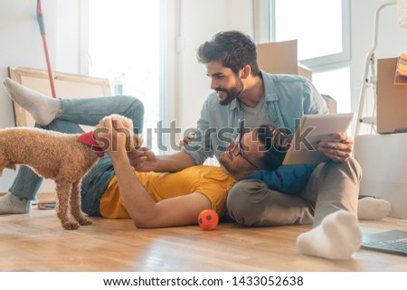 Happy homosexual couple sitting on floor and enjoying new home with poodle dog - Stock image