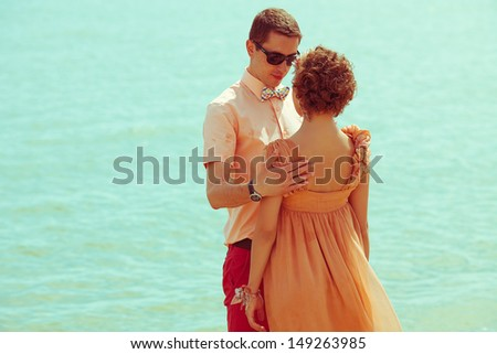 Happy honeymoon concept. Portrait of couple of young happy married hipsters in trendy clothes standing together on the beach. Sunny summer day. Copy-space. Outdoor shot