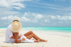 Happy honeymoon vacation at Paradise. Couple relax on the white sand of beach. Happy sea lifestyle. Young family, man and woman rest on the beach of ocean. Couple in love travel to island. Love travel