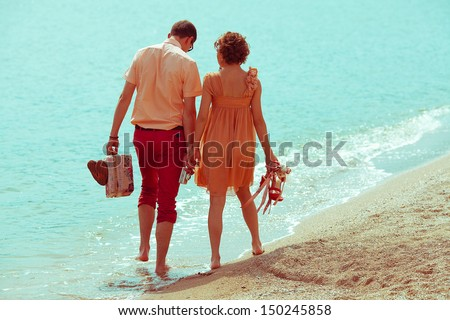Happy honeymoon (vacation) concept. Young happy married couple of hipsters walking on beach holding each other and holding their shoes, vintage suitcase and photocamera. Sunny summer day. Outdoor shot