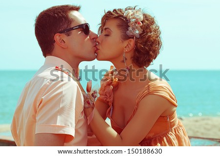 Happy honeymoon (vacation) concept. Young married couple of hipsters in trendy clothes kissing and hugging on the beach. Sunny summer day. Close up. Outdoor shot