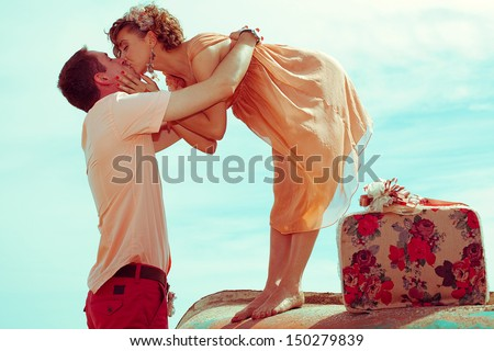 Happy honeymoon (vacation) concept. Young married couple of hipsters in trendy clothes standing on a boat, hugging and kissing. Sunny summer day, blue sky. Outdoor shot