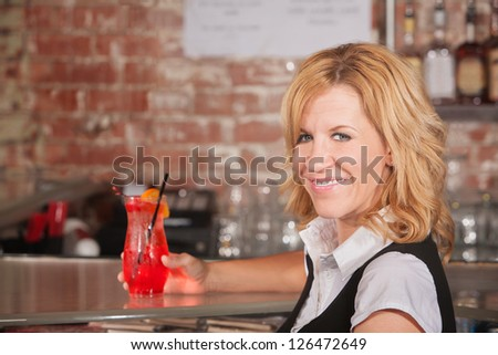 Happy hostess with alcoholic beverage glass in bar