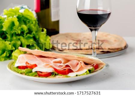 Happy hour - italian aperitif: glass of italian red wine with Italian flatbread - Piadina (Piada or piadina romagnola)  with mozzarella cheese, salad, tomatoes and italian ham -  prosciutto.