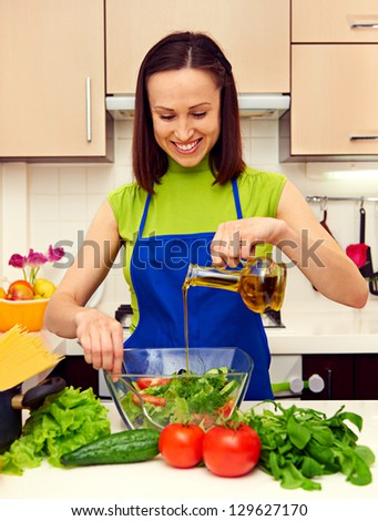 happy housewife adding oil in salad