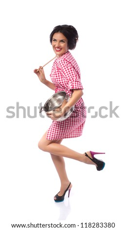 Happy housewife - Attractive smiling housewife posing on white background with a large stainless steel pot and a ladle, retro cooking concept