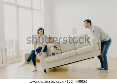 Happy husband and wife place sofa in living room, furnish their first home, help each other in renovation, little dog sits on couch, carry furniture together. Remodeling and renovation concept
