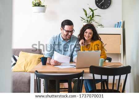 Happy husband and wife read good news online at laptop, smiling man holding documents receiving positive decision from bank, man and woman get email having mortgage or loan approved stock photo
