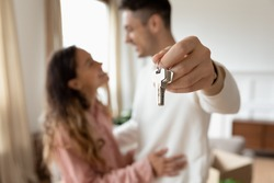 Happy husband and wife renters family. Young couple moving to first home showing keys to new house close up. Tenant, relocation day to own flat, ownership, bank lending, real estate agency ad concept