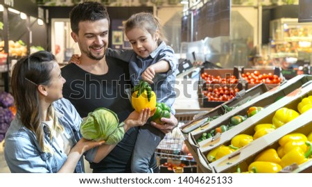 Happy husband and wife with a kid buys vegetables. Cheerful family of three choosing bell pepper and greens in vegetable department of supermarket or market. #1404625133
