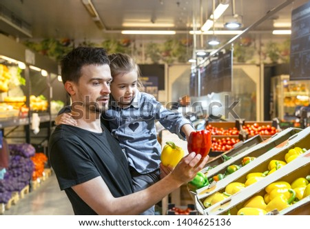Happy husband and wife with a kid buys vegetables. Cheerful family of three choosing bell pepper and greens in vegetable department of supermarket or market.