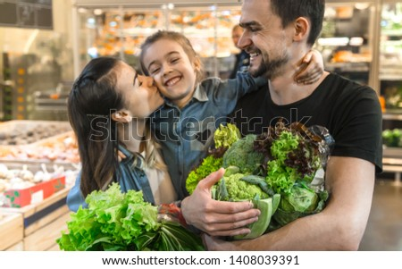 Happy husband and wife with a kid buys vegetables. Cheerful family of three choosing bell pepper and greens in vegetable department of supermarket or market. #1408039391