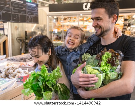 Happy husband and wife with a kid buys vegetables. Cheerful family of three choosing bell pepper and greens in vegetable department of supermarket or market. #1414490942