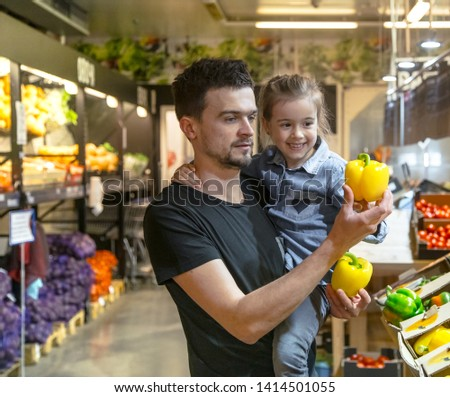 Happy husband and wife with a kid buys vegetables. Cheerful family of three choosing bell pepper and greens in vegetable department of supermarket or market. #1414501055