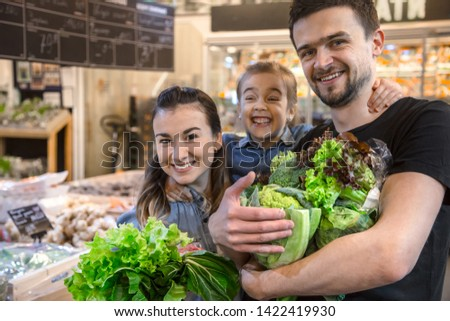 Happy husband and wife with a kid buys vegetables. Cheerful family of three choosing bell pepper and greens in vegetable department of supermarket or market. #1422419930