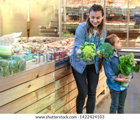 Happy husband and wife with a kid buys vegetables. Cheerful family of three choosing bell pepper and greens in vegetable department of supermarket or market. #1422424103
