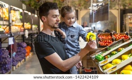 Happy husband and wife with a kid buys vegetables. Cheerful family of three choosing bell pepper and greens in vegetable department of supermarket or market. #1422424109