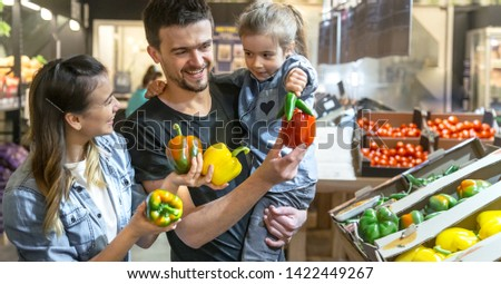 Happy husband and wife with a kid buys vegetables. Cheerful family of three choosing bell pepper and greens in vegetable department of supermarket or market. #1422449267