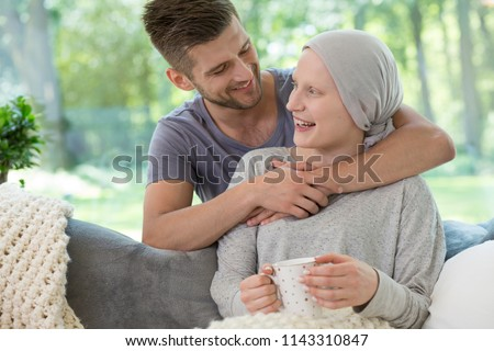 Happy husband hugging his wife recovering from chemotherapy for leukemia