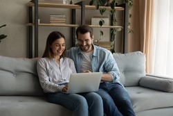 Happy husband wife newlyweds rest on sofa hold laptop choose furniture for new home buy consumer goods online. Young family couple using pc discuss flat renovation options planning trip on vacation