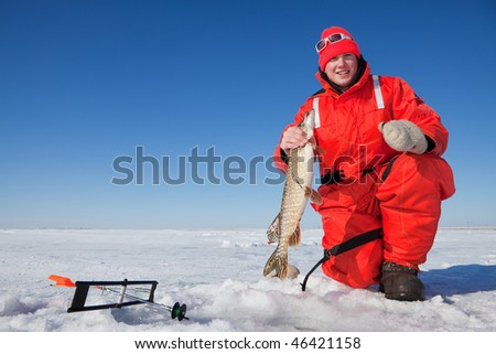 Happy ice fisherman holding a northern pike caught on a tip up
