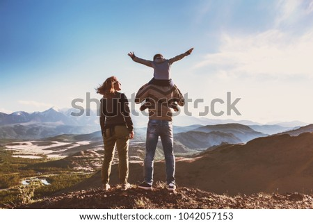Happy idyllic family of father mother and son stands against mountains and having fun #1042057153
